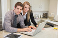 Smiling couple using laptop in kitchen Stock Photography