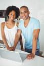 Smiling couple using laptop in the kitchen on counter Stock Photography