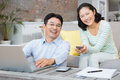Smiling couple using laptop and smartphone in the living room Royalty Free Stock Photography