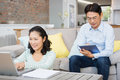 Smiling couple using laptop and tablet in the living room Royalty Free Stock Images