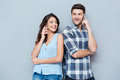 Smiling couple using mobile phones over gray background Royalty Free Stock Photo