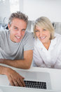 Smiling couple using their laptop in the morning looking at came camera sitting kitchen counter Stock Photo