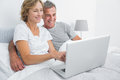 Smiling couple using their laptop together in bed at home bedroom Royalty Free Stock Photo