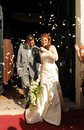 Smiling couple with white petals around them happy walking out of church after wedding flying the brides bouquet of lilies Royalty Free Stock Photography