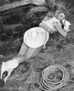 Smiling cowgirl lying on ground Royalty Free Stock Photo