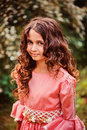Smiling curly child girl in pink princess dress on the walk in summer forest Royalty Free Stock Photo