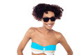 Smiling curly haired bikini model in dark shades Stock Photo