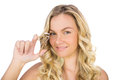 Smiling curly haired blonde holding eyelash curler on white background Royalty Free Stock Photos