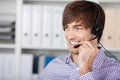 Smiling customer service executive using headset portrait of handsome in office Royalty Free Stock Image
