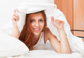 Smiling cute girl under the white sheets in bad at home Stock Photo