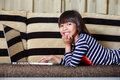 Smiling cute little asian girl with a laptop at home on sofa Royalty Free Stock Photo