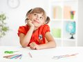 Smiling cute schoolgirl dreaming making homework Royalty Free Stock Photo