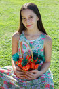 Smiling cute teen girl holding basket with carrot of sweet popco wicker popcorn for easter holiday sitting on green grass Stock Image