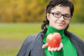 Smiling cute woman bites ripe apple young against background of autumn park Stock Photography
