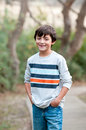 Smiling Cute young boy standing on sidewalk looking at camera Royalty Free Stock Photo