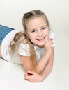 Smiling cutie cute little girl smiles sweetly lying on white floor Royalty Free Stock Photos