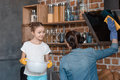Smiling daughter helping mother with housework at home