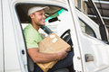Smiling delivery driver in his van holding parcel outside warehouse Royalty Free Stock Photo