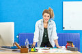 Smiling designer young product standing behind her desk leaning over several product sketches at the camera Royalty Free Stock Photo