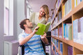 Smiling disabled student with classmate in library Royalty Free Stock Photo