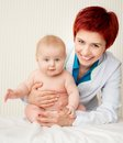 Smiling doctor with small baby Royalty Free Stock Photo