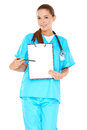 Smiling doctor with a blank clipboard attractive young nurse or in green scrubs holding up in her hand and pointing towards it Stock Photo