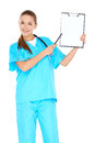 Smiling doctor with a blank clipboard attractive young nurse or in green scrubs holding up in her hand and pointing towards it Stock Image