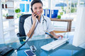 Smiling doctor having phone call and using her computer Royalty Free Stock Photo