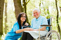 Smiling doctor with kind woman nurse taking care of senior lady patient in wheelchair Stock Photos