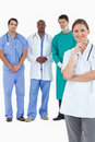 Smiling doctor with male staff members behind her Royalty Free Stock Images