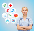 Smiling doctor over medical icons blue background Royalty Free Stock Photo