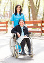 Smiling doctor and patient outdoors kind nurse taking care of an ill elderly women in wheelchair Royalty Free Stock Photos