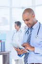 Smiling doctor using his tablet in the hospital Royalty Free Stock Photography