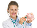 Smiling doctor woman listening piggy bank with stethoscope isolated on white Royalty Free Stock Image