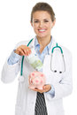 Smiling doctor woman putting euros banknote in piggy bank isolated on white Royalty Free Stock Image