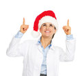 Smiling doctor woman in santa hat pointing up on copy space isolated white Royalty Free Stock Photo