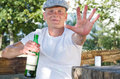 Smiling drunk defending his bottle of alcohol sitting woden table outdoors one hand extnded wards camera halt gesture while Stock Photo
