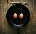 Smiling eggs in pan on wooden table Stock Image