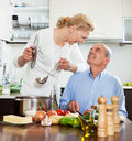 Smiling elderly couple and cooking together in kitchen domestic Stock Image
