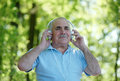 Smiling elderly man enjoying his music holding earphones with hands with a look of happy satisfaction as he relaxes Stock Image