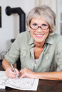 Smiling elderly woman doing a crossword puzzle attractive wearing glasses sitting at table in book Stock Photography