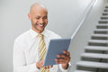 Smiling elegant young businessman using digital tablet against staircase in office Royalty Free Stock Photography