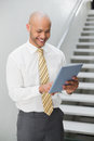 Smiling elegant young businessman using digital tablet against staircase in office Royalty Free Stock Images