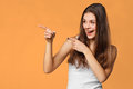 Smiling excited woman showing finger on copy space for product or text, isolated over orange background Royalty Free Stock Photo