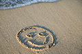 Smiling face on the beach a sandpainting of a symbol Stock Image