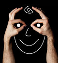 Smiling face between two showing sign ok hands show a with a smile is drawn inside black background Stock Photo