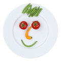 Smiling face from vegetables on plate isolated healthy eating a white background Stock Photos