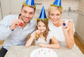 Smiling family in blue hats blowing favor horns celebration holidays and birthday concept happy with cake and candles Stock Images