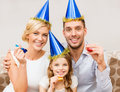 Smiling family in blue hats blowing favor horns celebration holidays and birthday concept three women wearing and Stock Images
