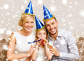 Smiling family in blue hats blowing favor horns celebration holidays and birthday concept three women wearing and Stock Photo